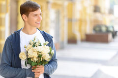 Handsome guy holding flowers Stock Image