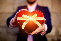 Handsome guy holding a gift in the form of heart for his mother Royalty Free Stock Photo