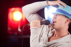 Handsome guy holding mic and singing. Royalty Free Stock Photo