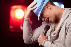 Handsome guy holding mic and singing. Stock Photo