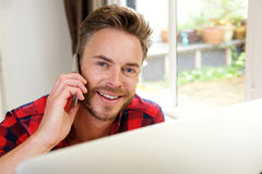 Handsome guy at home office on phone. Close up portrait of handsome guy at home office on phone Royalty Free Stock Photos