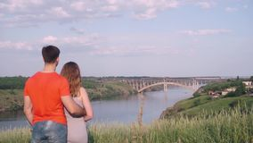 Handsome guy hugging girl from the back and they both bow down on nature, bridge. Overall plan stock footage