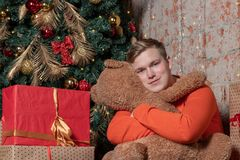 Handsome guy dreams and hugs the bear sitting under the tree surrounded by boxes of gifts. Christmas and gifts stock image