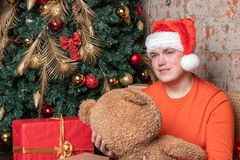 Handsome guy guy in santa claus hat hugs the bear sitting under the tree surrounded by boxes of gifts. Christmas and gifts royalty free stock image