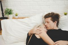 Handsome guy kiss girlfriend forehead softly with love. Lovers stay together on bed. Boyfriend, girlfriend hug or embracing each royalty free stock photography