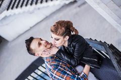 Handsome guy kisses his girlfriend standing on the stairs. The concept of romantic relationships royalty free stock photography