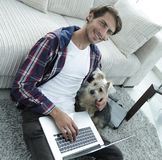 Handsome guy with laptop hugging his dog and sitting near the couch. In a stylish living room Royalty Free Stock Photo