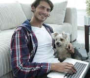 Handsome guy with laptop hugging his dog and sitting near the couch. In a stylish living room Stock Photo