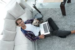 Handsome guy with laptop hugging his dog and sitting near the couch Royalty Free Stock Image