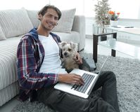 Handsome guy with laptop hugging his dog and sitting near the couch. In a stylish living room Stock Images