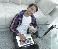 Handsome guy with laptop hugging his dog and sitting near the couch Stock Photography