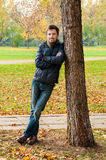 Handsome guy leaned against a tree Royalty Free Stock Photography