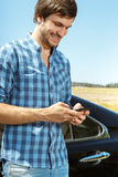 Handsome guy leaning on his car. Handsome young man using phone while leaning on car Stock Photos