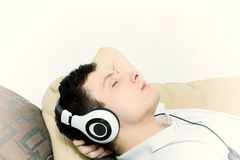 Handsome guy listening to music on headset with eyes closed stock photo