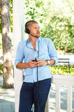 Handsome guy listening to music via smartphone Stock Images
