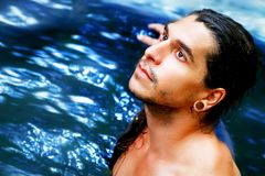 A handsome guy with long hair, brown eyes and piercings on a background of blue water. Waterfalls in the rain forest.  Stock Photography