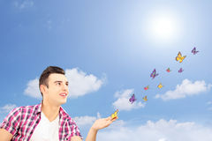 Handsome guy looking at butterflies Royalty Free Stock Photography