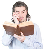 Handsome guy looks into book and thinks isolated. Young dark haired caucasian man in light blue shirt reads book and scratches his head in confusion isolated on Stock Image