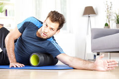 Handsome Guy Lying on Side with Foam Roller Royalty Free Stock Image
