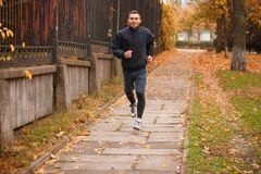 A handsome guy makes a run in the autumn park. The concept of sport. A handsome young sporty guy dressed in sportswear makes a run in the autumn park. The Stock Photo