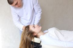 Handsome guy massage therapist doing head massage for girl clien. Educated cosmetologist conducts procedure to relieve tension in head and gives advice on care Royalty Free Stock Photography