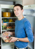 Handsome guy with meat near opened refrigerator Stock Images