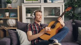 Handsome guy melomaniac is listening to music in headphones and playing the guitar relaxing at home on sofa in leisure stock video