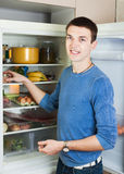 Handsome guy near opened refrigerator Stock Images