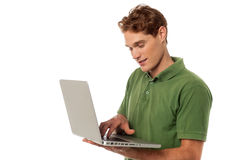 Handsome guy operating laptop Stock Images