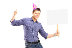 Handsome guy with party hat holding a panel and giving thumb up Stock Images