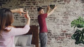 Handsome guy is picking place on brick wall to hang modern picture while his girlfriend is making frame with her fingers. Handsome young guy is picking place on stock video footage