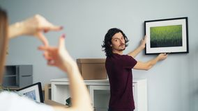 Guy picking place for picture when girlfriend making frame with fingers. Handsome guy is picking place on wall to hang modern picture while his girlfriend is stock video footage