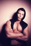Handsome guy posing in hood. Bodybuilder Stock Image