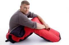 Handsome guy posing in red sleeping bag Royalty Free Stock Images