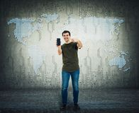 Handsome guy presenting a trendy smartphone. Positive smiling man showing a new phone over abstract modern background with world royalty free stock photography