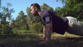 Handsome guy press-up in summer at the open air. stock footage