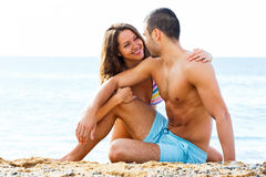 Handsome guy and pretty girlfriend resting on sand Stock Photography