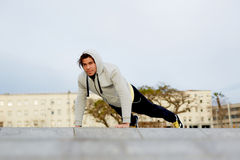 Handsome guy push ups outdoors. Young attractive man dressed in sweatshirt doing push ups outdoors at early morning royalty free stock photos