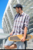 Handsome guy resting on staircase with skate. Pensive young man is standing on steps with skateboard Royalty Free Stock Images
