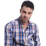 Handsome guy romantically looking at the camera. Close up of a handsome guy romantically looking at the camera while wearing a checkered unbuttoned shirt on royalty free stock photography