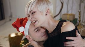 Handsome guy in santa claus hat in love hugging girlfriend in christmas night or New Year. Happy young couple in love stock video
