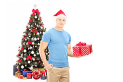 Handsome guy with santa hat holding a gift and posing in front o Royalty Free Stock Image