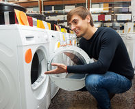 Handsome guy selecting washing machine. In hypermarket and smiling Stock Photography