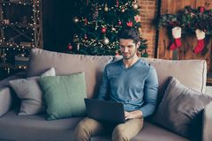 Handsome guy sit couch use computer search christmas season sales to buy fairy magic presents having house with