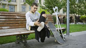 Handsome guy sits on the bench in the park listening to music on his cellphone. Crutches and skateboard are nearby. Attractive man sitting on the bench in summer stock video footage