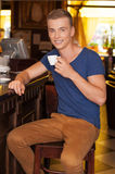 Handsome guy sitting and drinking espresso. Stock Photos