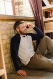 Handsome guy sitting on floor by the window talking on phone. Man at home in casual clothes talking on phone sitting on floor Royalty Free Stock Images