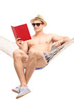 Handsome guy sitting in a hammock and reading Stock Photography