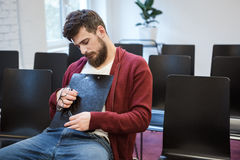 Handsome guy sitting and sleaping hugging clipboard Stock Image
