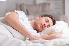 Handsome guy sleeps in his bed Stock Photos